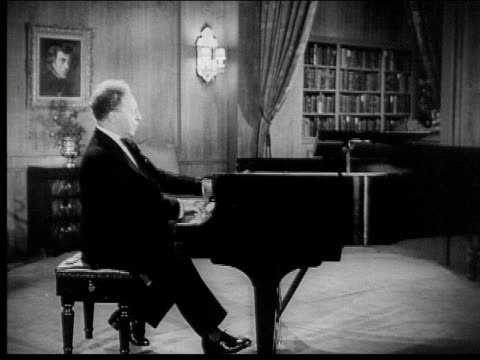 Arthur Rubinstein plays Chopin's Polonaise in A flat a grand piano in a lavishly decorated living room to a group of formally dressed older men and...