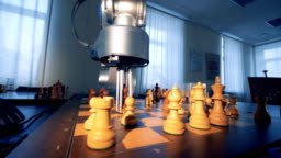 Artificial intelligence concept. Innovative modern robotic arm playing chess with a man. 4K.