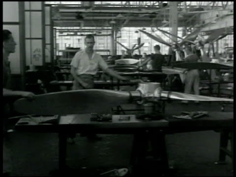DEFENSE Artillery barrel being moved by crane in foundry VS United Aircraft factory men w/ propeller blades assembling propellers men assembling...
