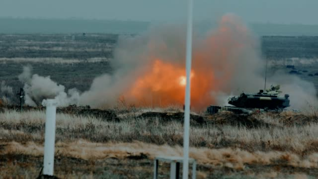 artillery tank rides in the steppe and shoots - shooting a weapon stock videos & royalty-free footage