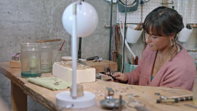 vidéos et rushes de artisan jeweler crafts metal with flat hand file in studio. - profession créative