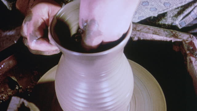 1964 cu artisan shaping a clay vessel on a potter's wheel / aldermaston, berkshire, england - potter stock videos & royalty-free footage