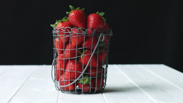 artisan wire basket of organic, local strawberries against black background - juicy stock videos & royalty-free footage