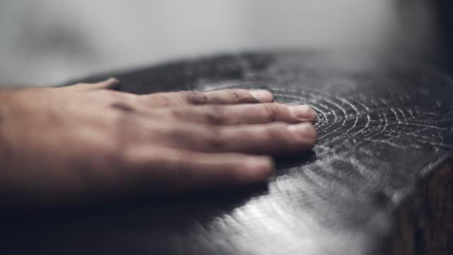 cu artisit's hands rubbing paint into a wood block - handgemacht stock-videos und b-roll-filmmaterial