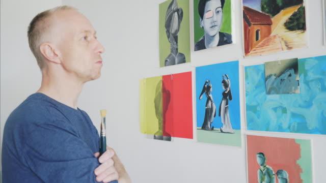 Artist analyzing paintings.