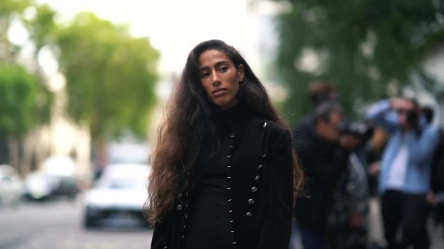Artist and singer Ciinderella B wears a black military jacket with buttons a black dress during London Fashion Week September 2018 on September 14...