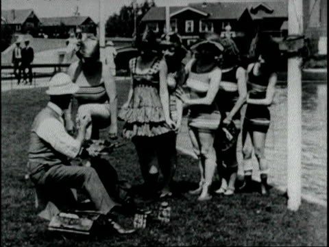artist at the beach paints identification symbols on bathing beauties before they go in the water apparently modeled after a french fad bathing... - 1918 stock videos and b-roll footage