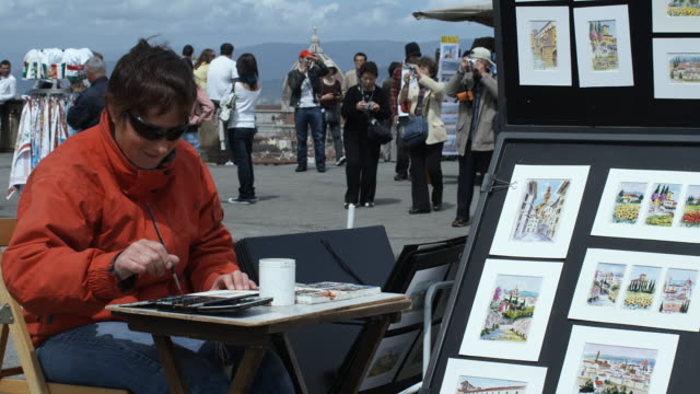 ms pan artist at work with watercolor paints, piazzale michelangelo, florence, tuscany, italy - michelangelo artist点の映像素材/bロール