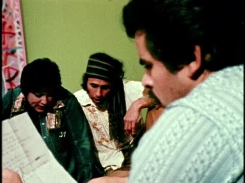 artist carlos almaraz playing guitar as artists judithe hernandez, roberto de la rocha and gilbert lujan singing along, los angeles, california, usa,... - 1974点の映像素材/bロール