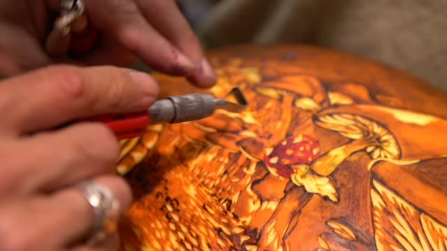 vidéos et rushes de artist carving into pumpkin - sculpture production artistique