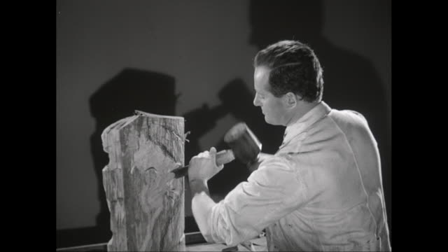 MS Artist chiselling wooden statue with mallet in workshop / United States