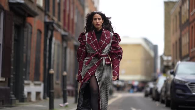 artist ciinderella b wears sunglasses, earrings, a red black and white houndstooth pattern print long trench coat, black shoes, during london fashion... - トレンチコート点の映像素材/bロール