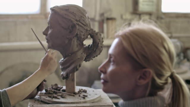 Artist creating sculpture with live model