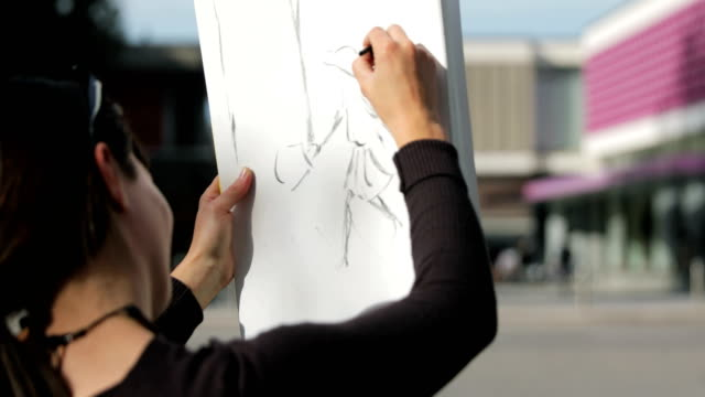 Artist Drawing a Sketch on a City Street