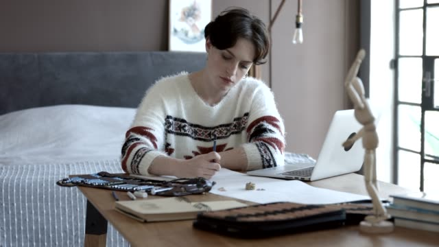 stockvideo's en b-roll-footage met artist drawing while looking at laptop in bedroom - tekening
