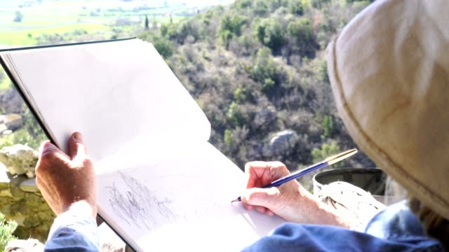 Artiste de dessin avec un crayon, en vue d'une belle vallée, vidéo