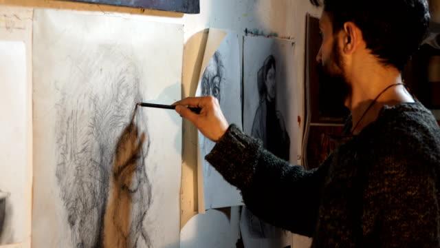 vídeos de stock, filmes e b-roll de artist draws a portrait  with a pencil - 4k video - só um adulto de idade mediana