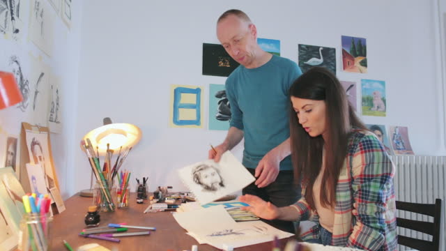 Artist explaining to a female student about a few sketches.