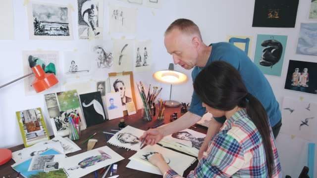 Artist explaining to a female student about drawing method.