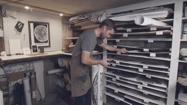 vidéos et rushes de artist getting his artwork ready to mail. - designer