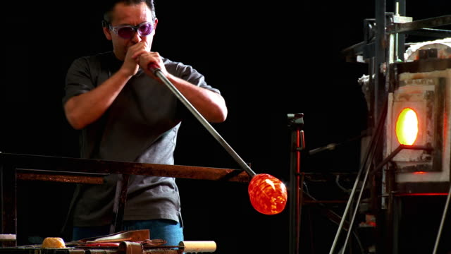 ms artist glassblower blowing into blowpipe and shaping glass, placing piece in glory hole furnace, santa barbara, california, usa - glasbläser stock-videos und b-roll-filmmaterial
