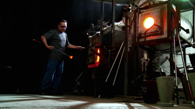 ws artist glassblower gathering molten glass by pulling blowpipe out of furnace and walking towards camera with red hot piece of glass stuck to tip of blowpipe, santa barbara, california, usa - glasbläser stock-videos und b-roll-filmmaterial