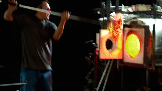 ms zi cu artist glassblower pulling finished piece out of glory hole with punty and using gravity and centrifugal force to create flower form, santa barbara, california, usa - glasbläser stock-videos und b-roll-filmmaterial