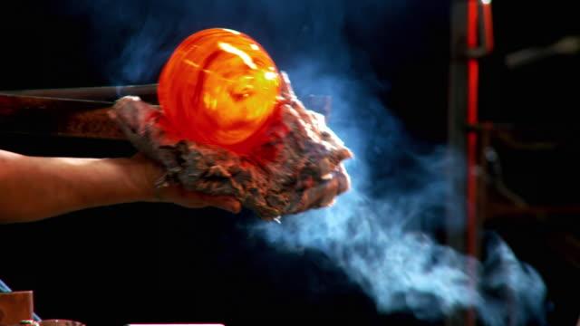 cu zo ms artist glassblower shaping molten glass ball by hand using wet newspaper, santa barbara, california, usa - glasbläser stock-videos und b-roll-filmmaterial