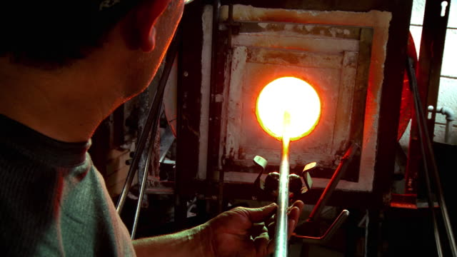 cu artist glassblower standing in front of glory hole with blowpipe resting on ball bearings of yoke while slowly rotating back and forth to evenly heat up glass piece, santa barbara, california, usa - glasbläser stock-videos und b-roll-filmmaterial