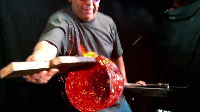 MS ZI CU Artist glassblower widening diameter of flower form using wooden paddle, Santa Barbara, California, USA