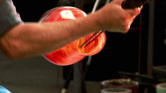 cu artist glassblower's hand opening up and sculpting shape of molten bowl with jacks, santa barbara, california, usa - glasbläser stock-videos und b-roll-filmmaterial