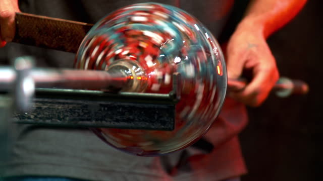 CU Artist glassblower's hands transferring glass from blowpipe to punty, Santa Barbara, California, USA