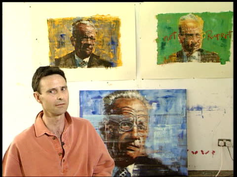 artist john keane along past pictures of rupert murdoch pinned to wall pan keane looking at painting he produced featuring city traders dollar bills... - ピンを刺す点の映像素材/bロール