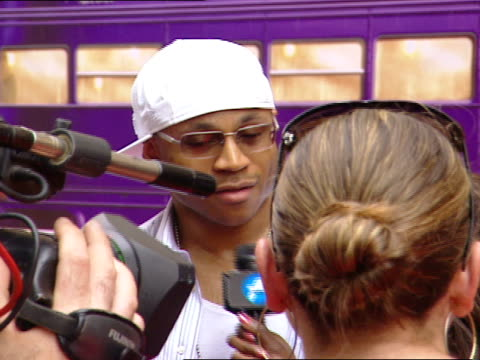day * artist ll cool j cap sunglasses standing on red carpet near radio city music hall talking to press african american female reporter - radio city music hall stock videos and b-roll footage