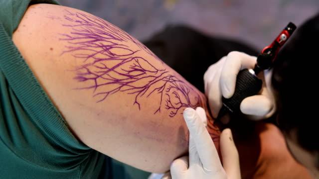 artist making tattoo on male customer - giuntura umana video stock e b–roll