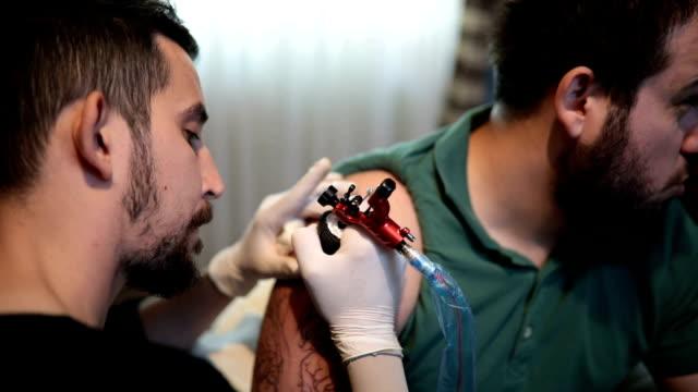 vídeos y material grabado en eventos de stock de artista haciendo tatuaje en cliente masculino - articulación humana