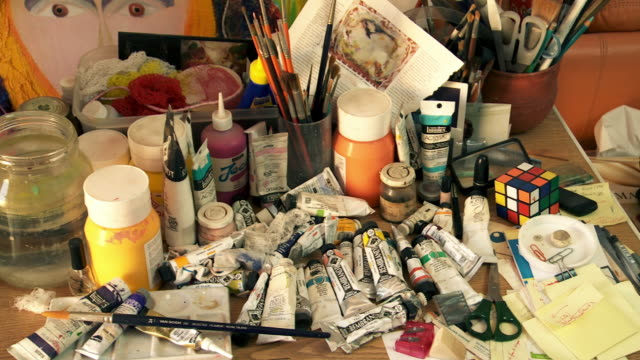 Artist materials and Artist's Hand dipping brush into water