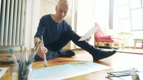 vídeos y material grabado en eventos de stock de artista pintando sentado en el piso. - arte