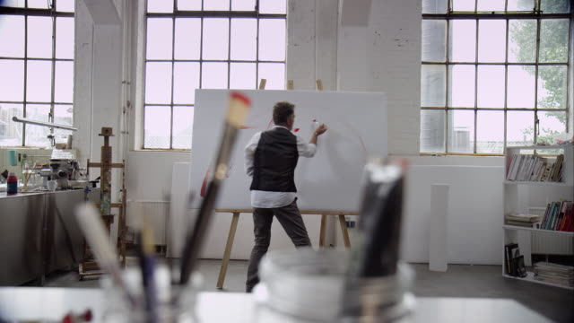 stockvideo's en b-roll-footage met artist painting with red color on canvas - studio shot