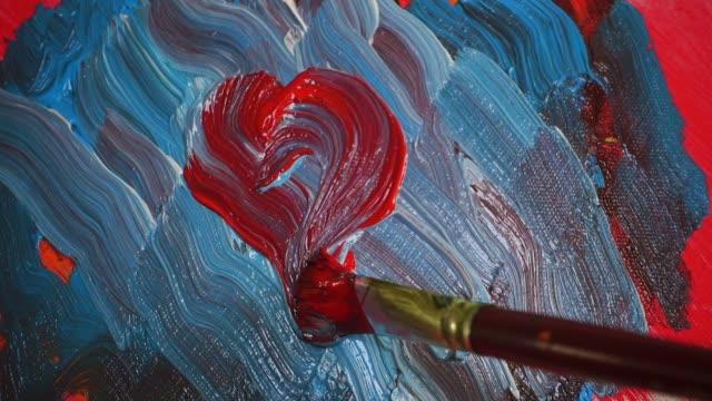 stockvideo's en b-roll-footage met artist paints heart on canvas - verfkwast