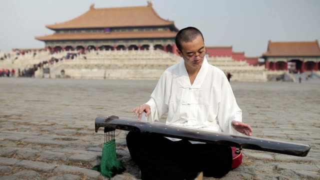Artist playing the Guqin in Forbidden City in Beijing, China