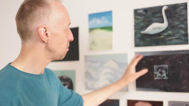 stockvideo's en b-roll-footage met kunstenaar presenteert zijn schilderijen in de galerie. - tentoonstelling