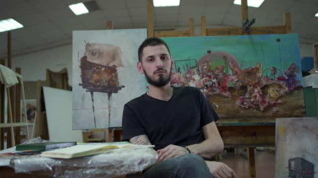 vídeos de stock, filmes e b-roll de artista sentado à mesa com suas pinturas aquarelas atrás dele - sentando