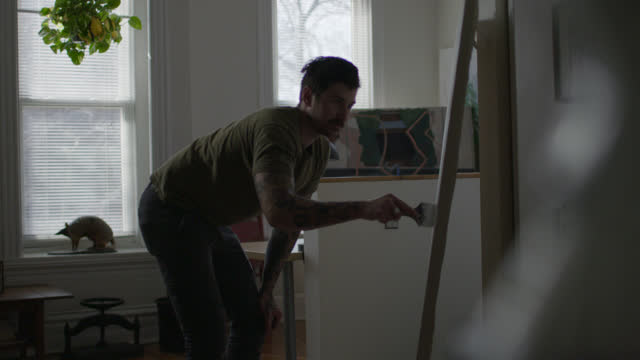 WS SLO MO. Artist spreads primer up stretched canvas with paintbrush in apartment workshop.