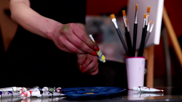 artist squeezes the paint from the tube on palette - paint tube stock videos and b-roll footage