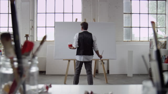 artist starts painting on canvas - easel stock videos and b-roll footage