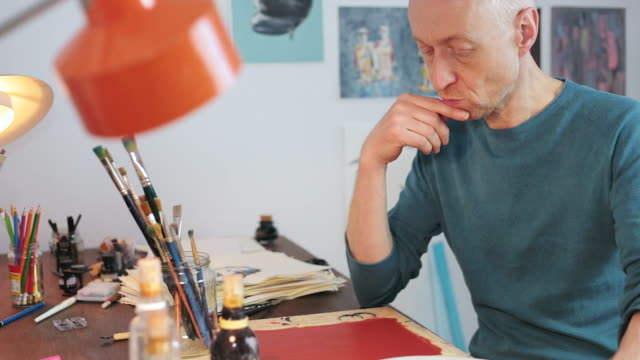 Artist thinking and preparing a new paint.