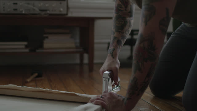 ms slo mo. diy artist uses staple gun to assemble stretched canvas and hammers staple into wooden frame with mallet. - diy stock videos and b-roll footage
