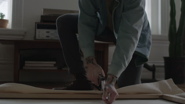 ms slo mo. diy artist uses stretching pliers and staple gun to clamp and attach canvas to frame in apartment studio. - ホッチキス点の映像素材/bロール