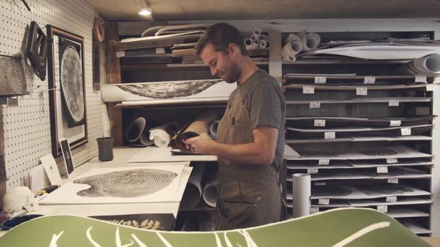 artist using his phone in his studio - sending stock videos & royalty-free footage